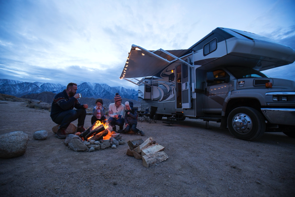 A family around a campfire in front of a class C motorhome.