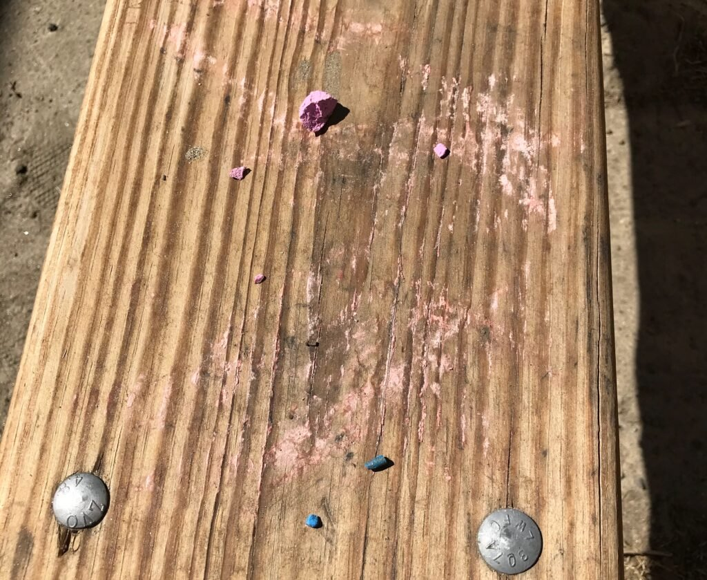 picnic table seat covered in chalk markings and bits